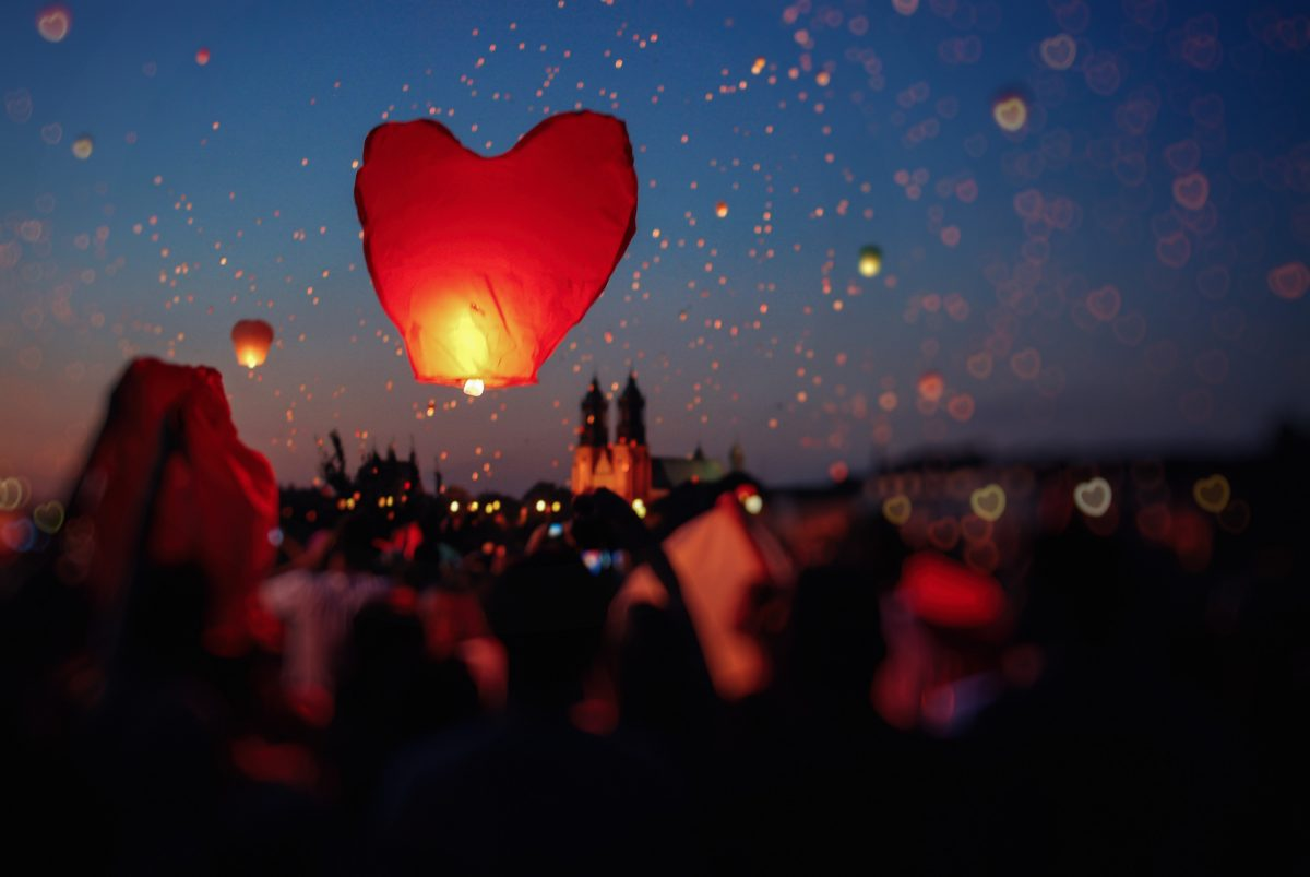 A heart-shaped lantern takes flight as thousands of similar lanterns float up to the sky in the background in Poznan, Poland