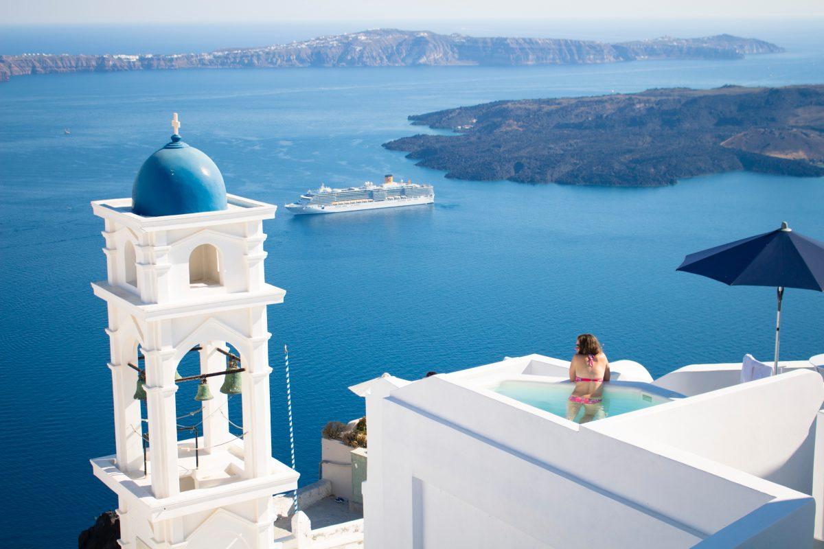 A woman swims in a pool overlooking the sea in Santorini, Greece