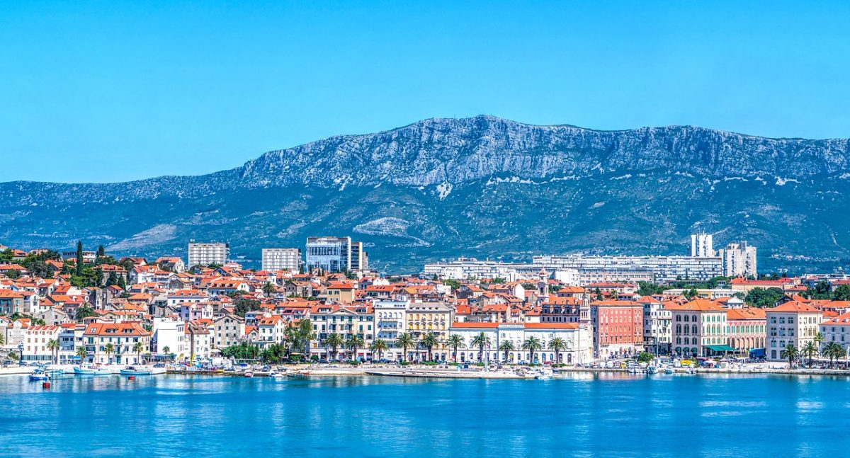 Various buildings line the shore as a mountain range stands in the background in Split, Croatia