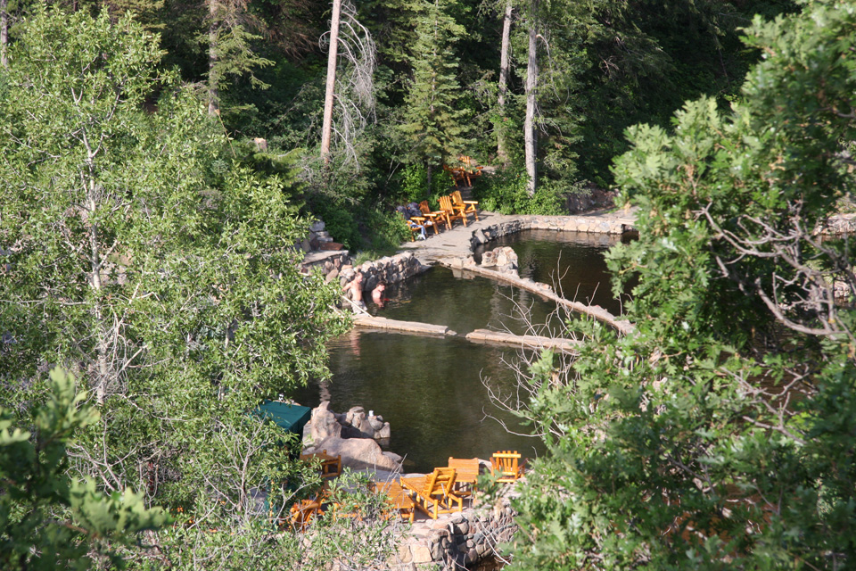 Two guests take a dip in the hot springs surrounded by lounge chairs and trees in Strawberry Park Hot Springs, Colorado