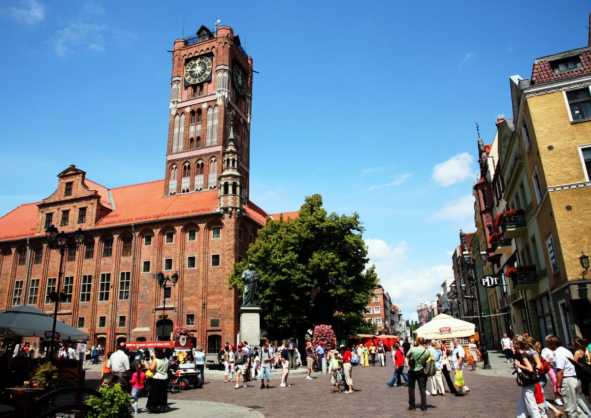 People walking near the clock tower on the streets of Torun's Medieval Town in Torun, Poland