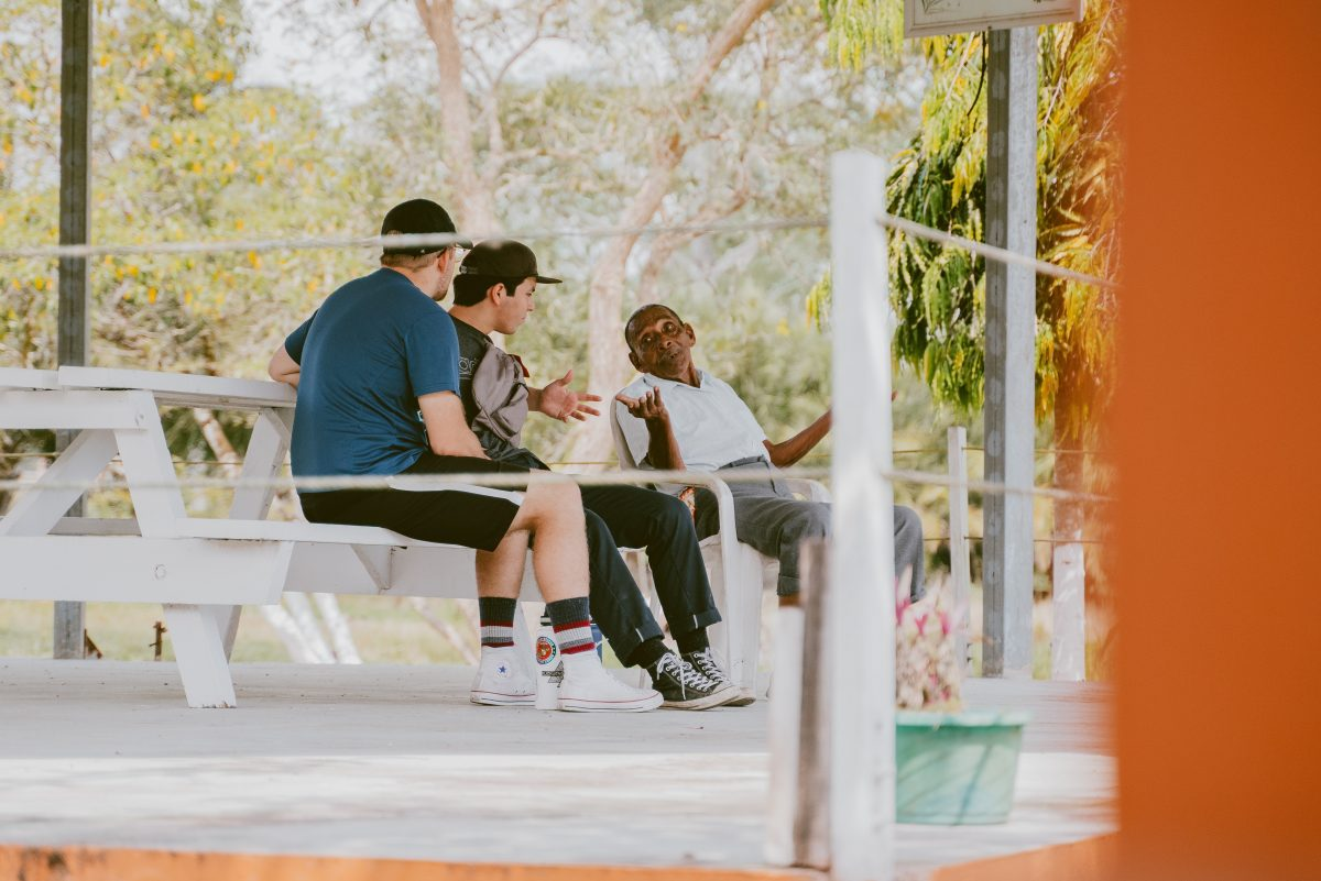 Two foreign men conversing with a Belizean man.