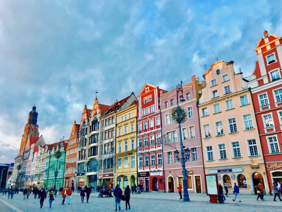 People walking along a street lined with colorful houses in Market Square, Wroclaw, Poland