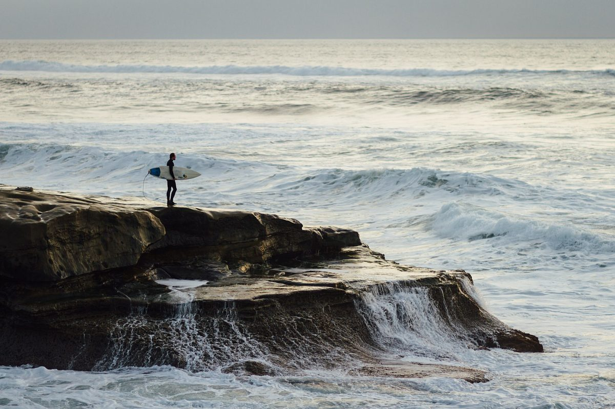 Surfer standing on a cliff amidst great waves