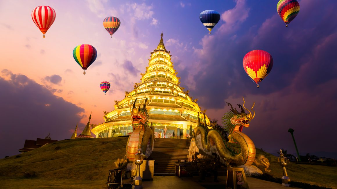 Hot-air balloons flying over Wat hyua pla kang , Chiang Rai, Thailand