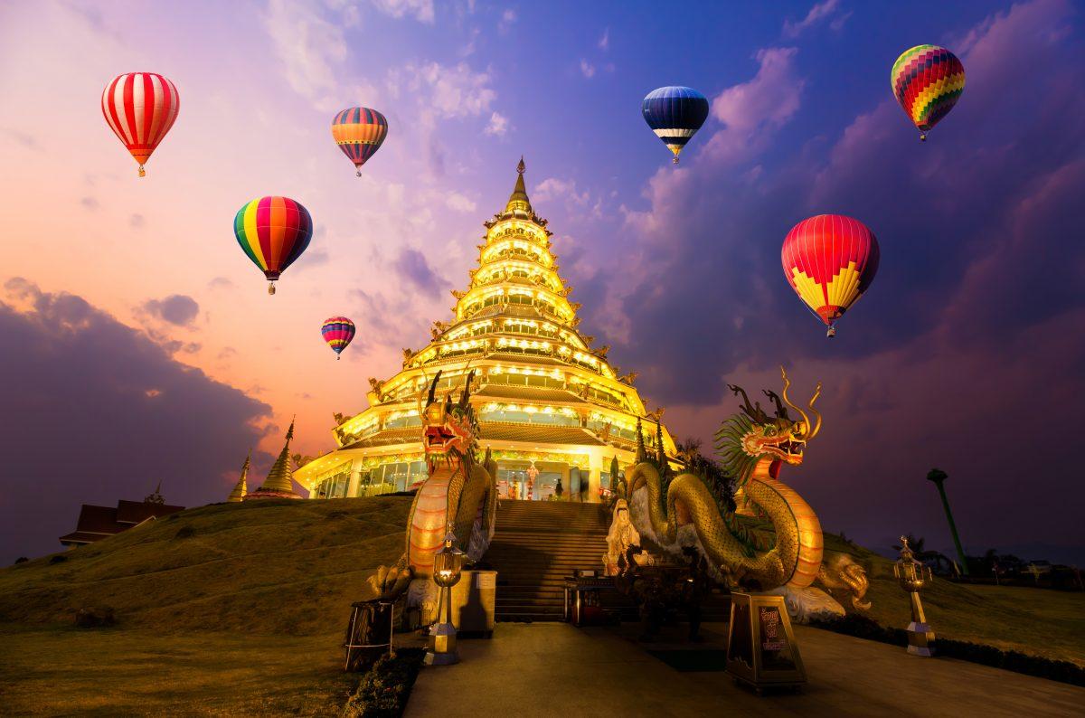 Hot-air balloons flying over Wat hyua pla kang , Chiang Rai, Thailand