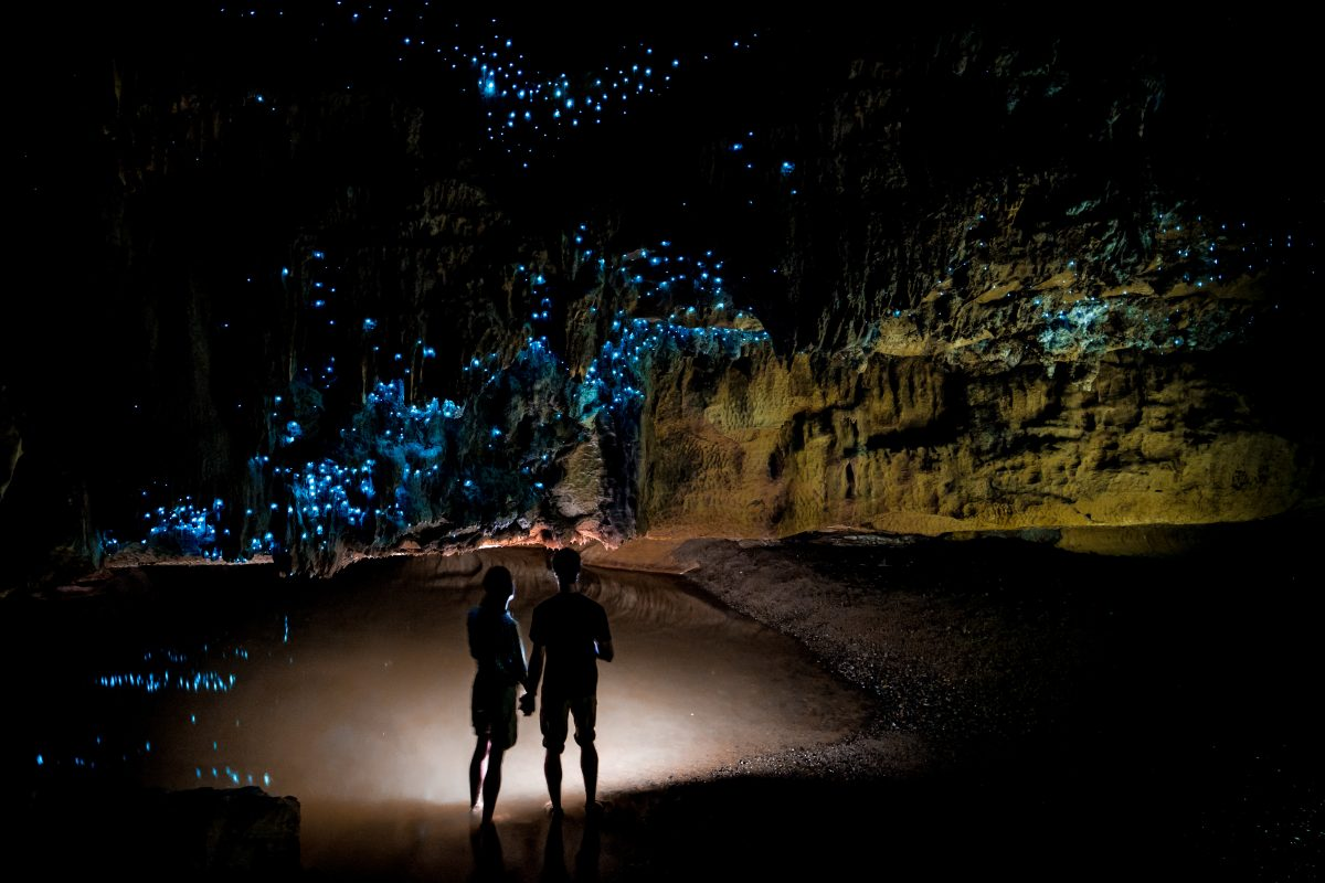 Couple under New Zealand GlWorm Sky in Waipu Cave
