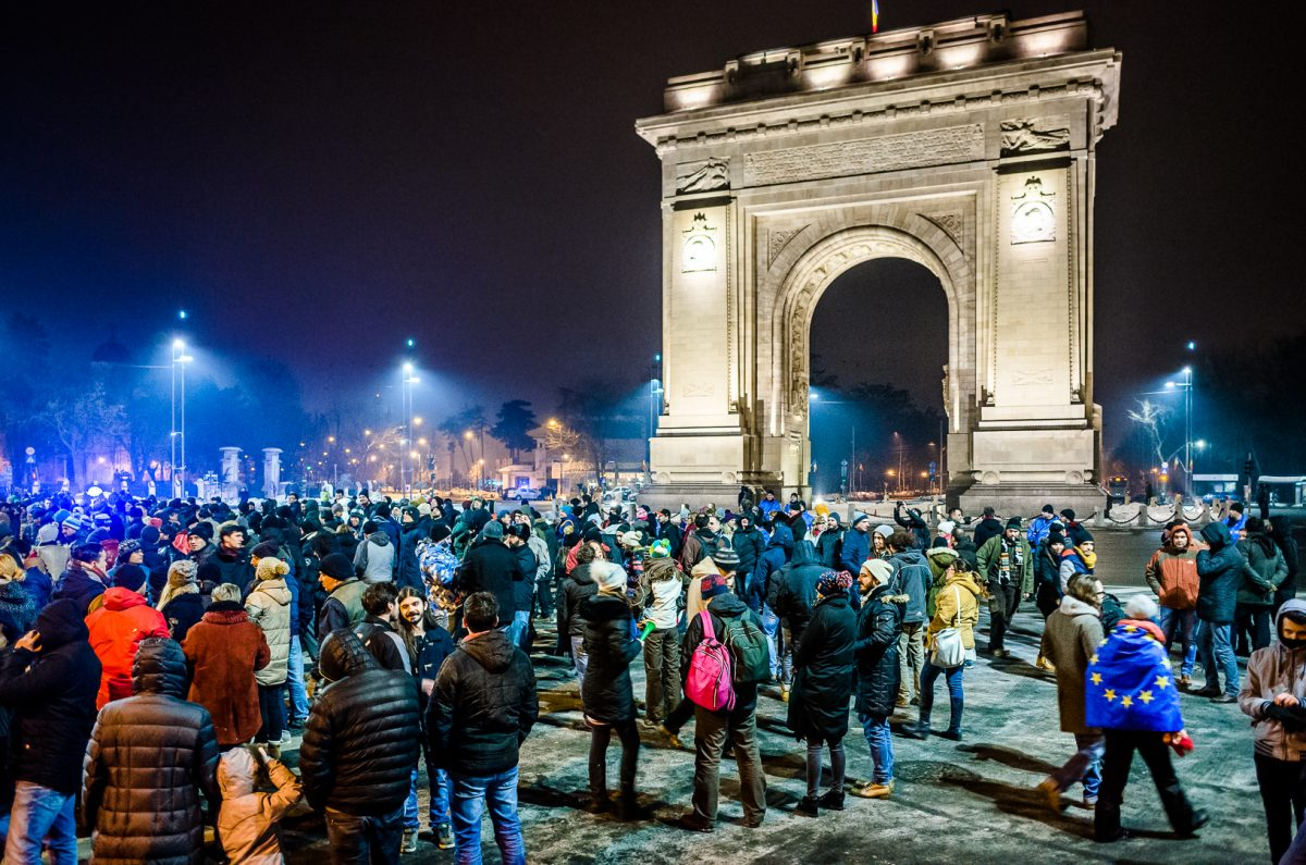 Busy people talking to one another with Arcul De Triumf on the background