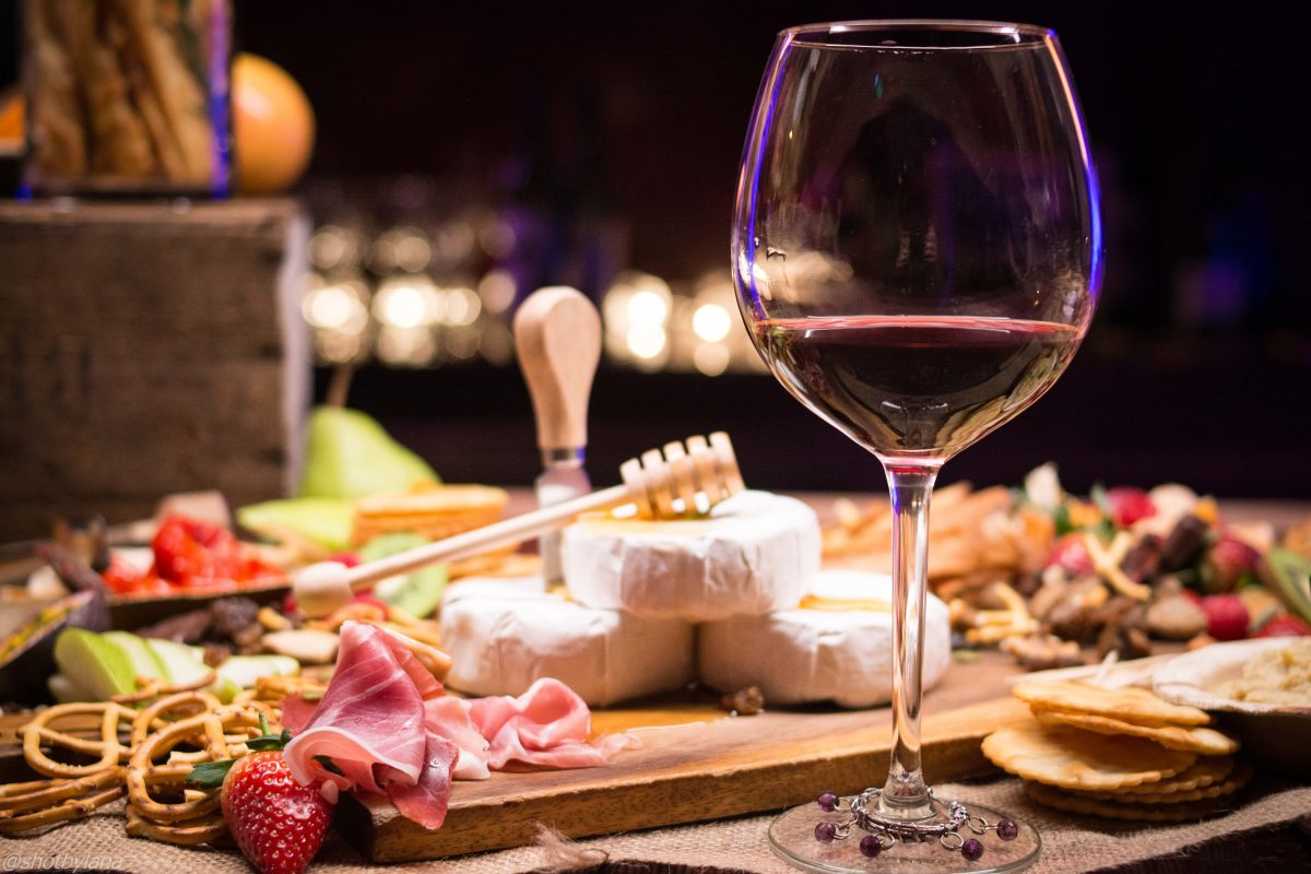 Red wine and a platter of cheeses spread over the table.