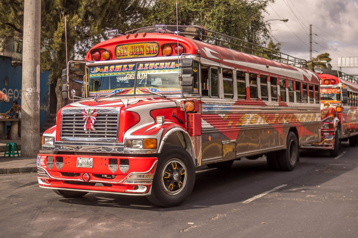 two red guatemalan public busses on the road