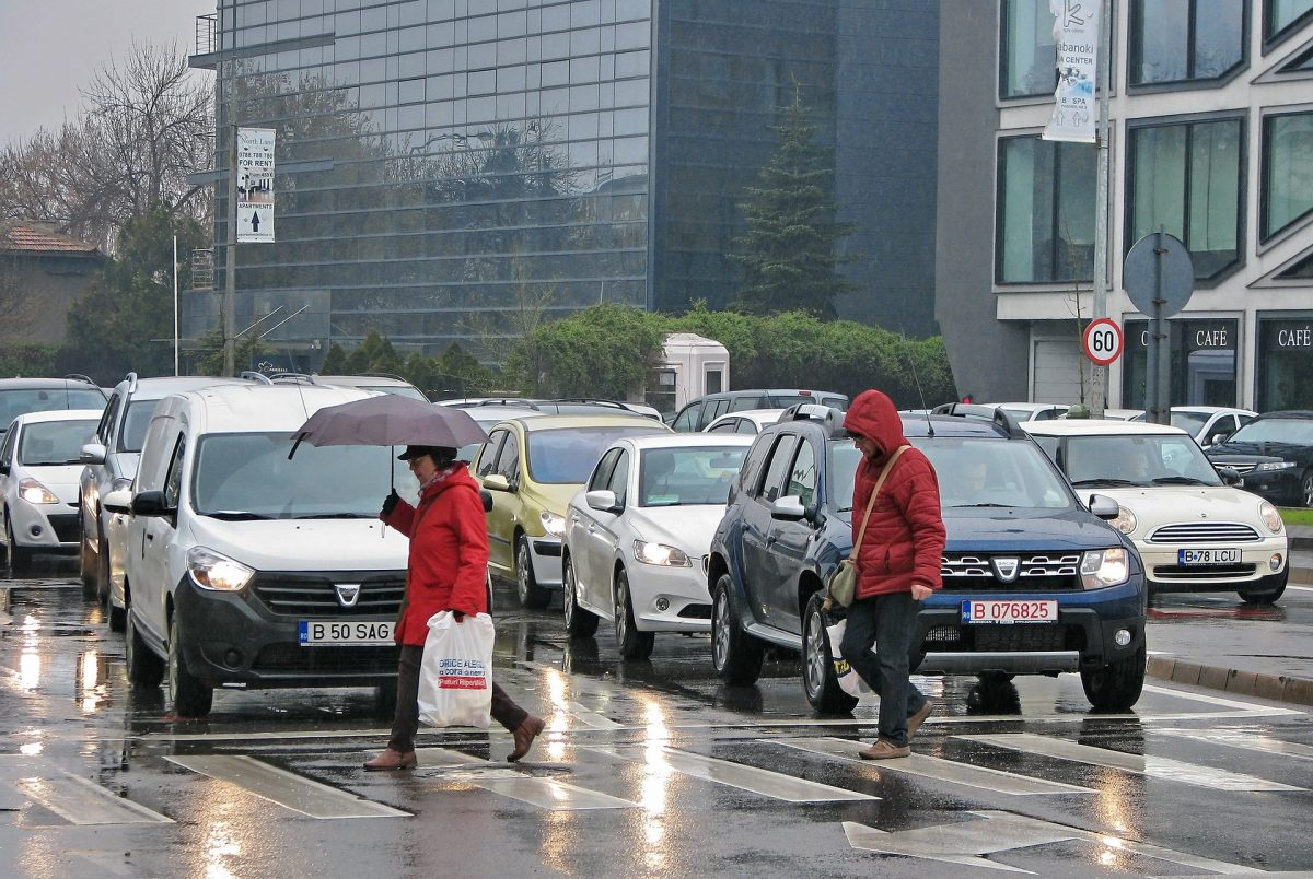 People Crossing Pedestrian Lane While Raining