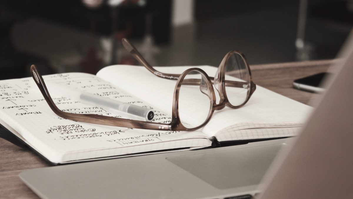 brown glasses, black pen,  and journal on top of laptop
