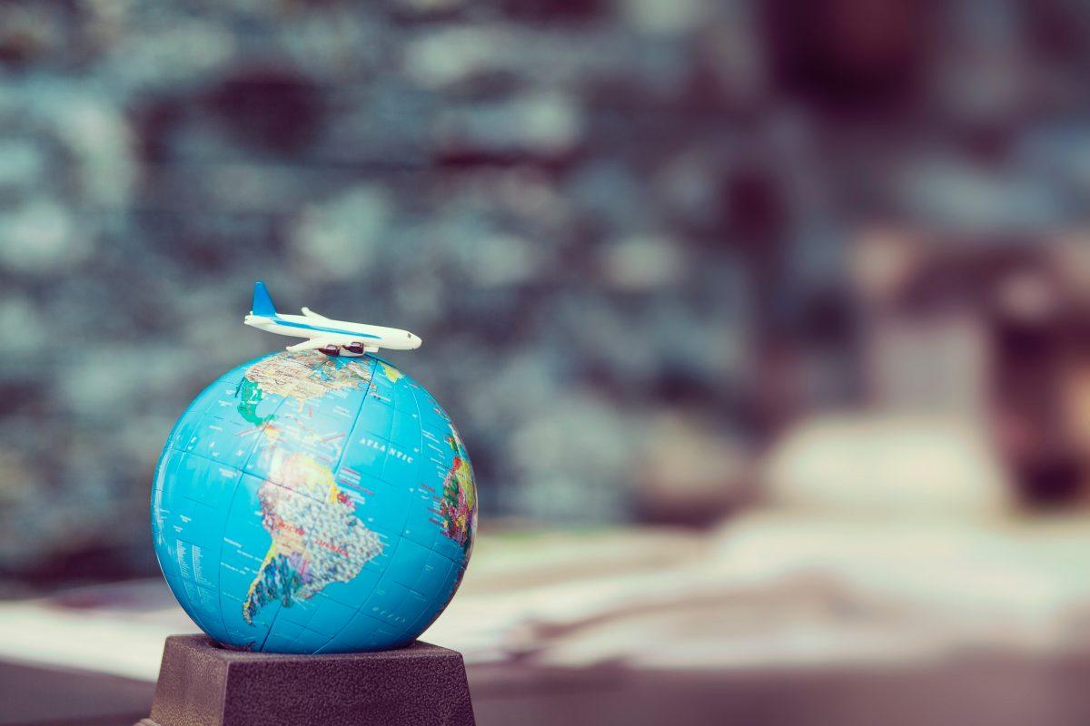 Miniature airplane figure on top of small world globe