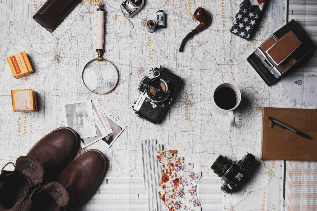 camera, leather shoes, magnifying glass, journals and other travel items on top of paper USA map
