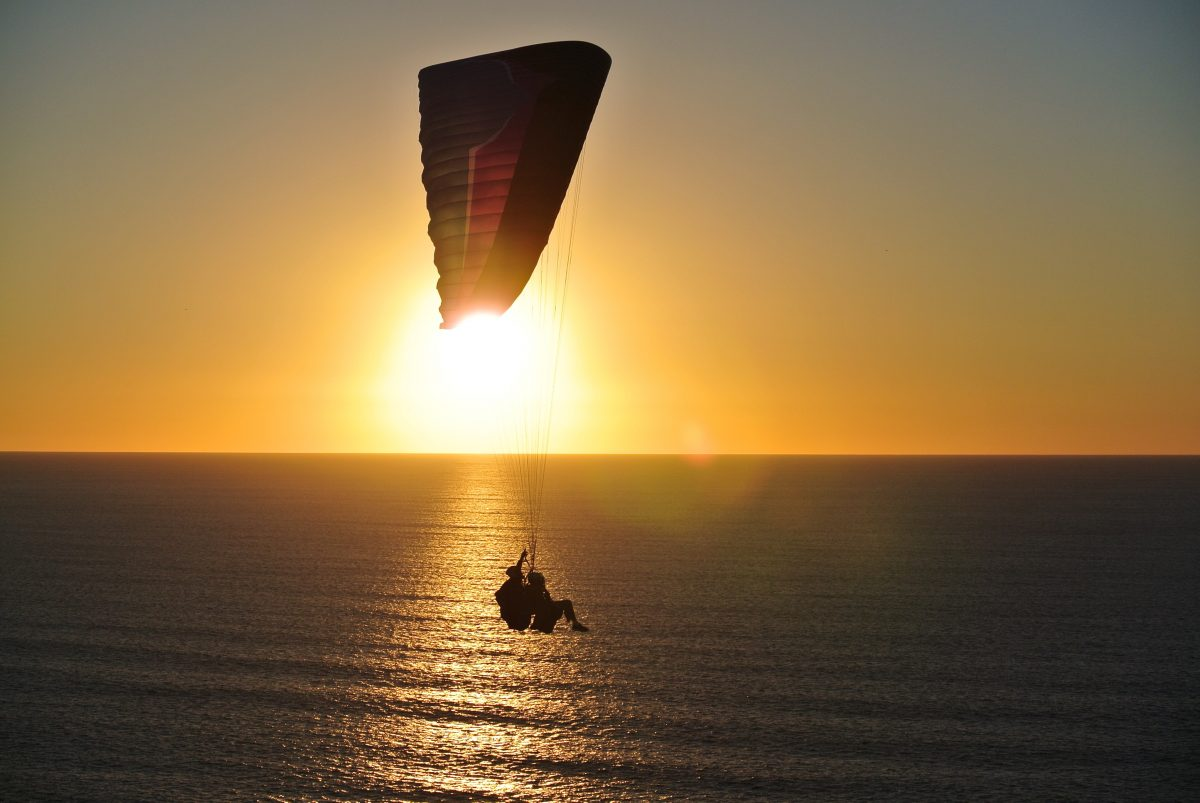 Two people paragliding over Torrey Pines State Beach, San Diego