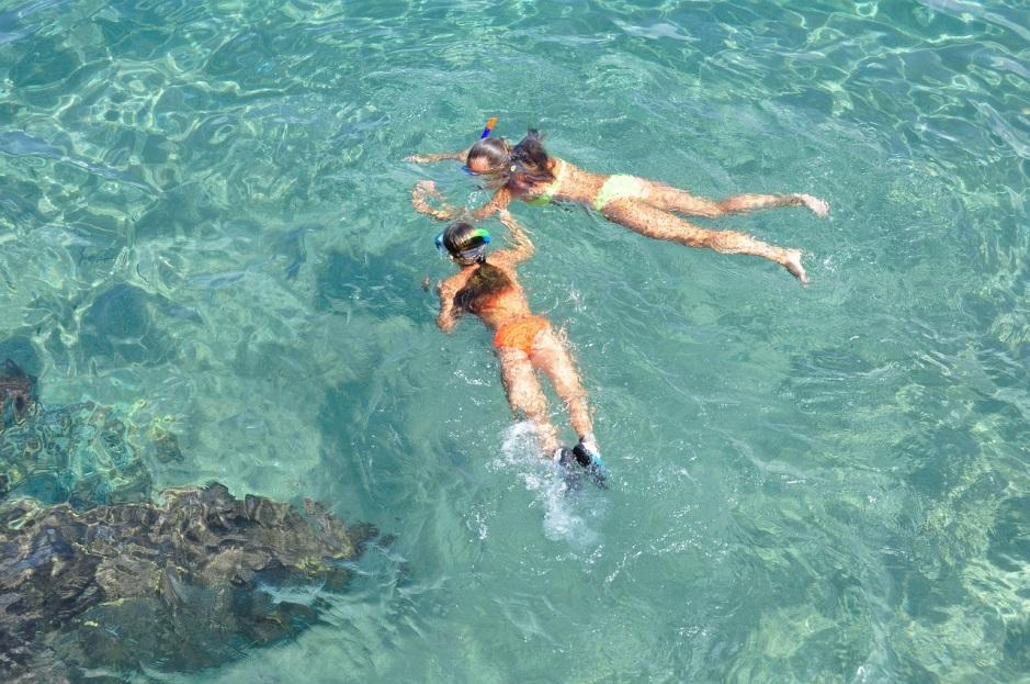 women snorkeling on clear and bright water