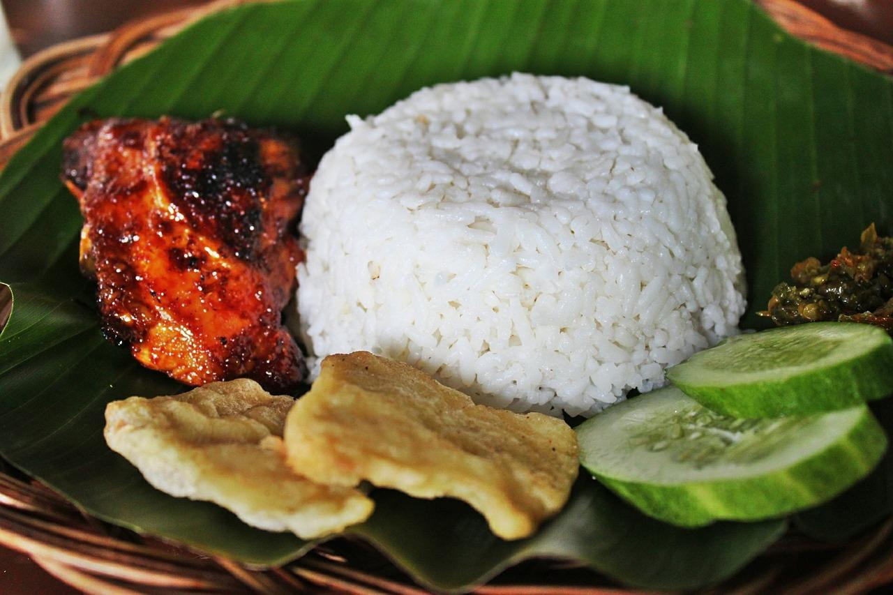 photo of grilled chicken and rice on banana leaf