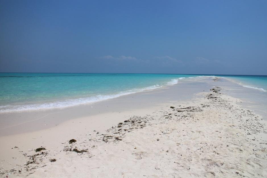 photo of a beach sand lagoon with a clear blue sky
