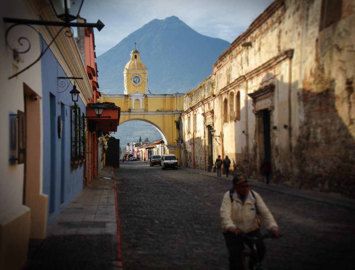 A cobblestone street in Antigua, Guatemala with a volcano in the background