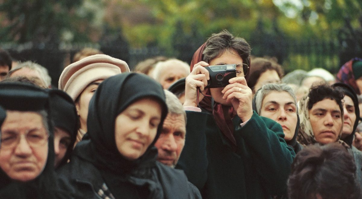 Man capturing picture surrounded by Romanian people