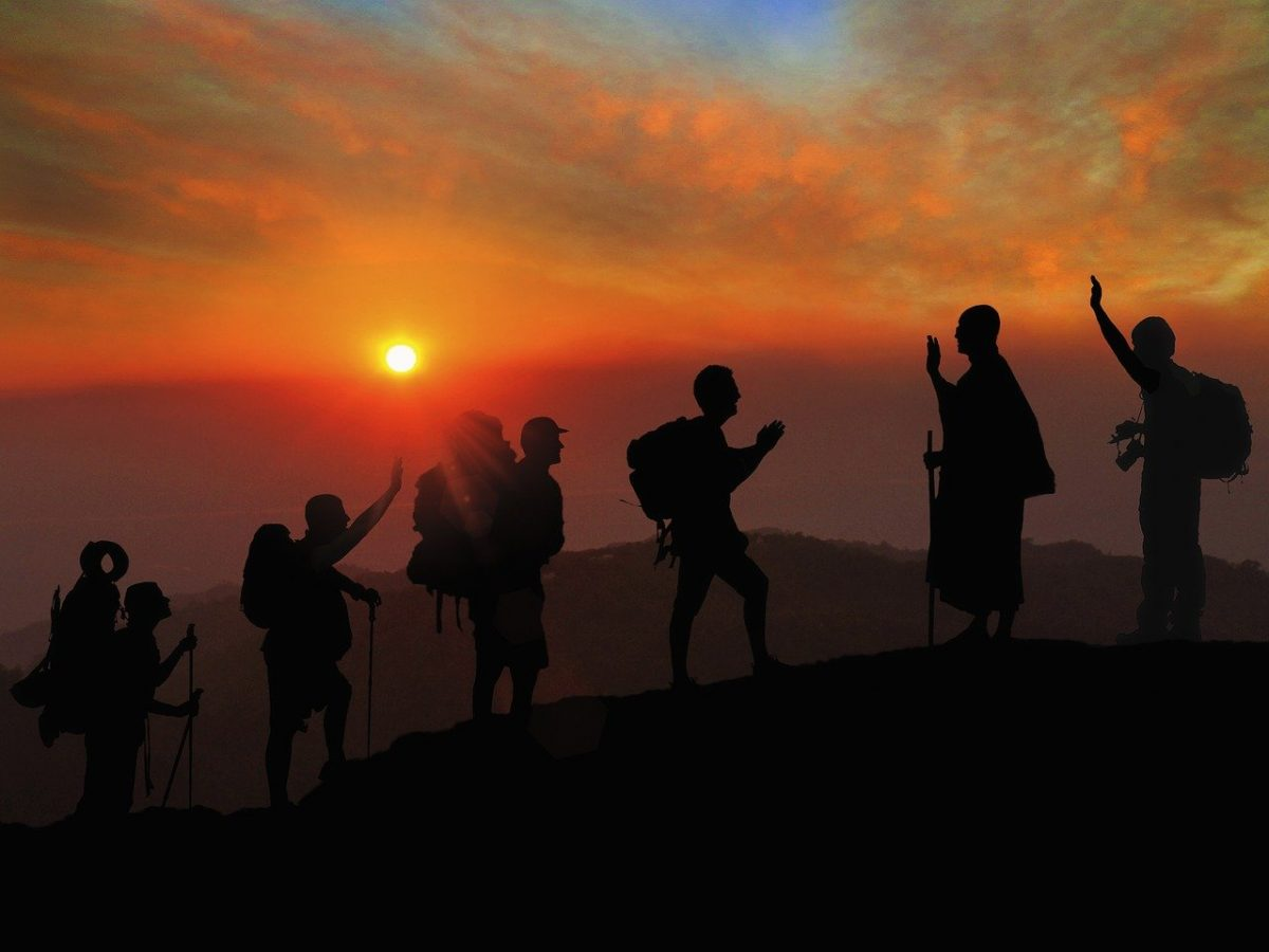 a group of people mountain trekking at sunset
