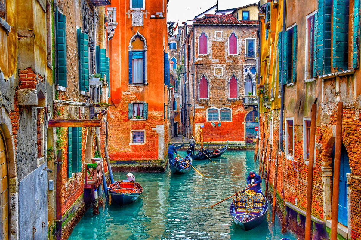 Venetian canal alley surrounded by colorful orange and brown buildings
