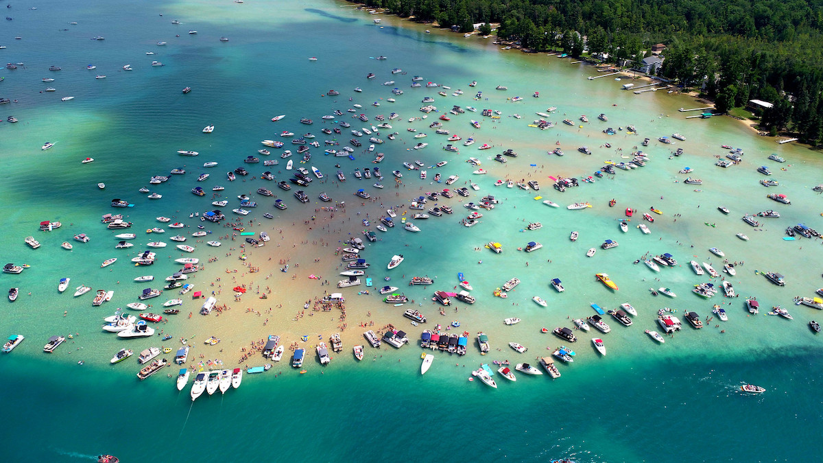 Colorful boats are anchored around the famous Torch Lake sandbar