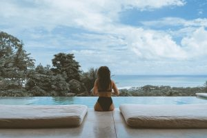 Photo of the backside of a woman with long hair wearing a black two-piece swimsuit sitting on the edge of an infinity pool with two mattresses on either side of her, beyond the pool are the tops of trees and a distant view of the ocean with a cloudy blue sky