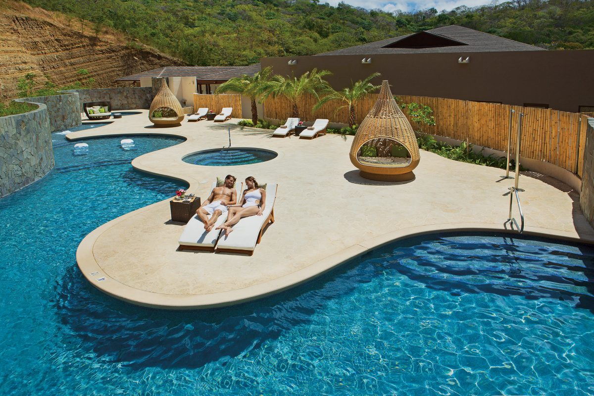 Guests lying down on white poolside recliners in Dreams Las Mareas Costa Rica