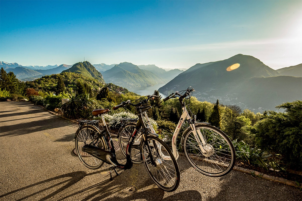 Bicycles parked beside flowering plants while overlooking Lugano mountains