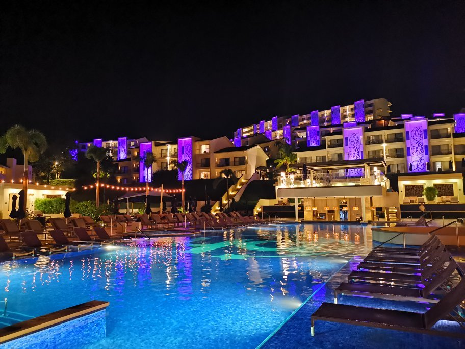 Planet Hollywood Beach Resort's outdoor pool and hotel, well-lit at night