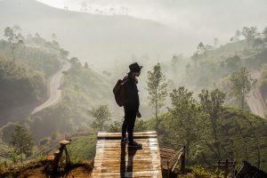 A man stands at the end of a trail overlooking the mountainous region below in Bandung, Indonesia