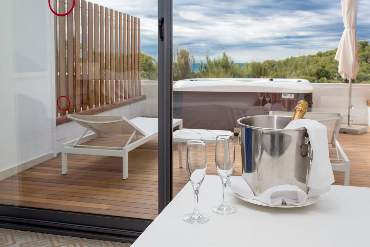 Champagne and glasses sit on a table in a hotel room with a hot tub and lounge chair on the terrace in Dolce by Wyndham Sitges, Sitges, Spain