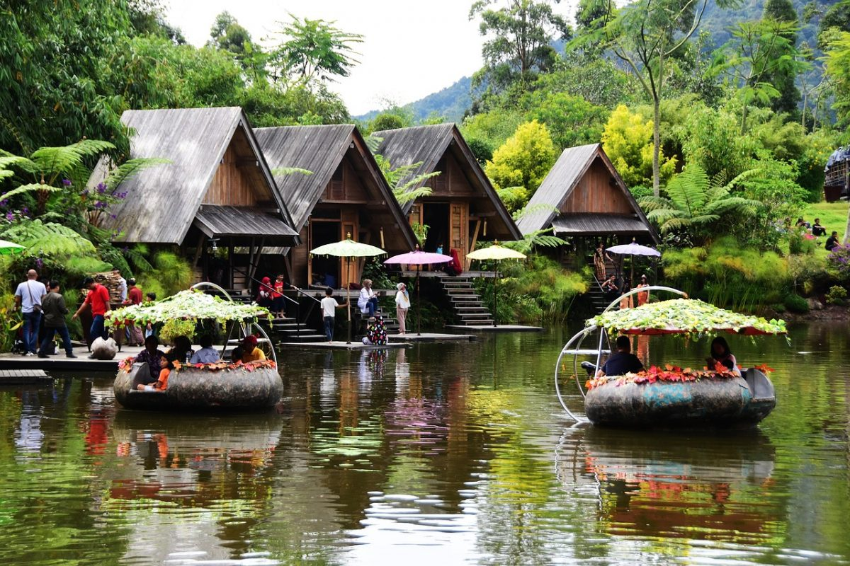 Floral boats float on a lake lined with huts on the edges in Dusun Bambu, Bandung, Indonesia