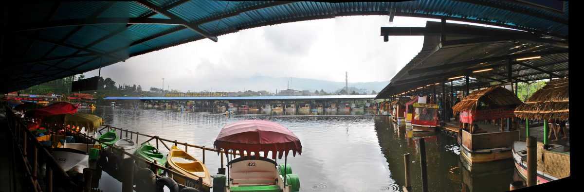 Floating food stalls and boats line the edges of a lake in Lembang Floating Market, Bandung, Indonesia