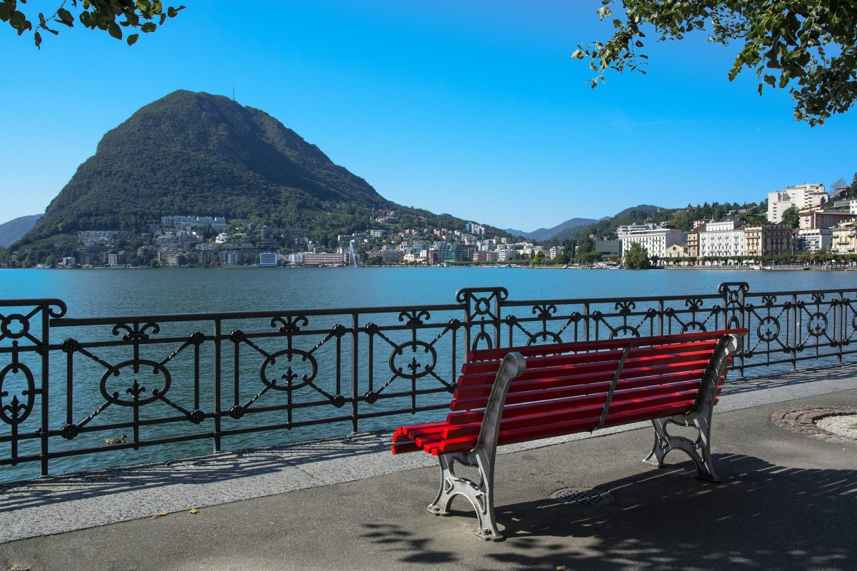 Red Bench facing Lake Lugano on a sunny day