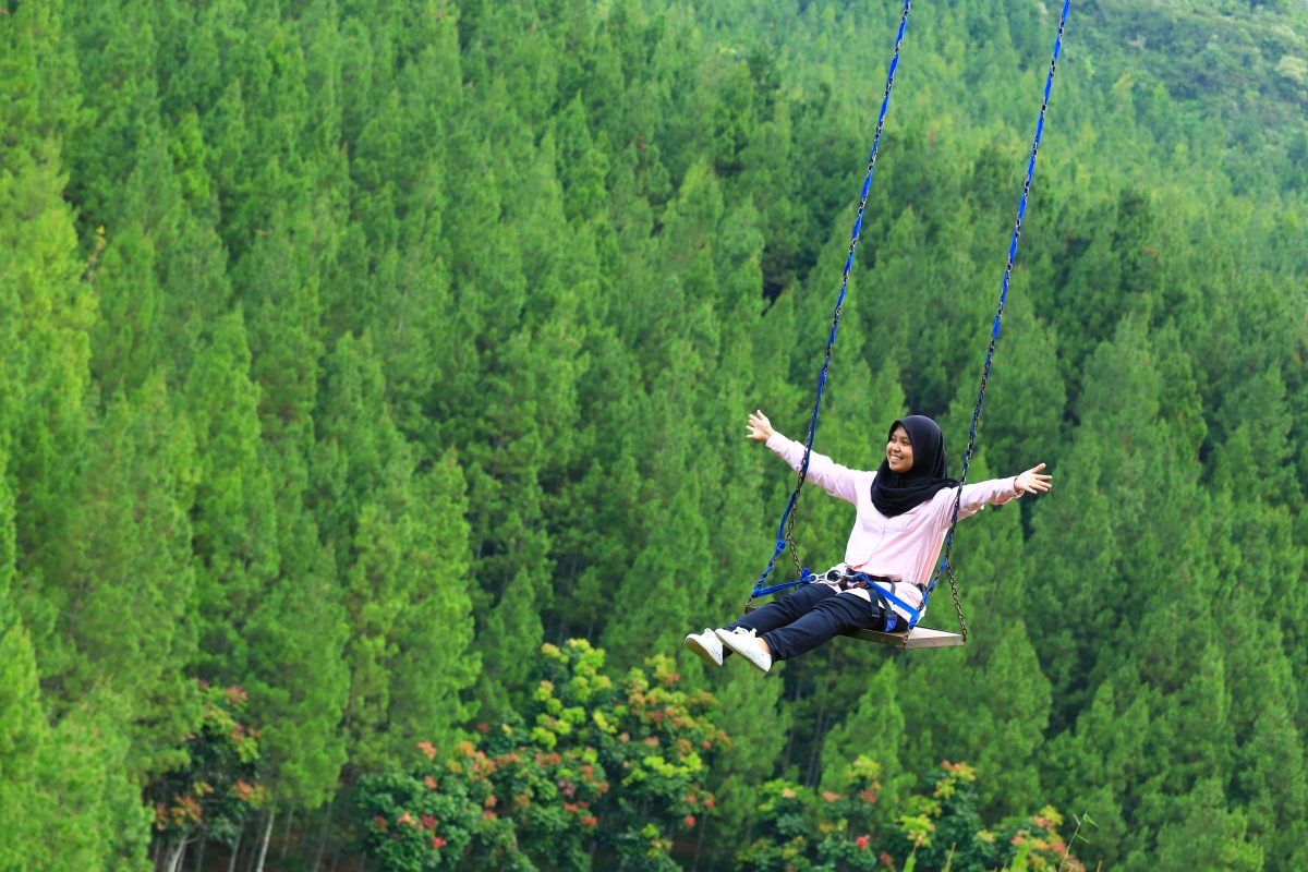 A woman swings over trees with open arms and a wide smile in Maribaya, Bandung, Indonesia