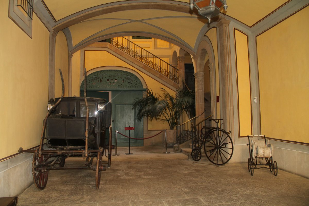 An old carriage, bike, and stroller are displayed in front of a staircase at Museu Romantic in Sitges, Spain