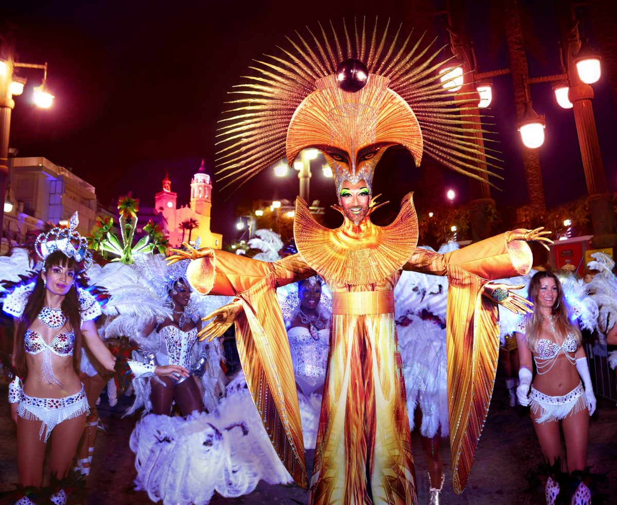 A man dressed in a vibrant costume spreads his arms as women in feathery costumes walk behind him during the Sitges Carnival in Sitges, Spain