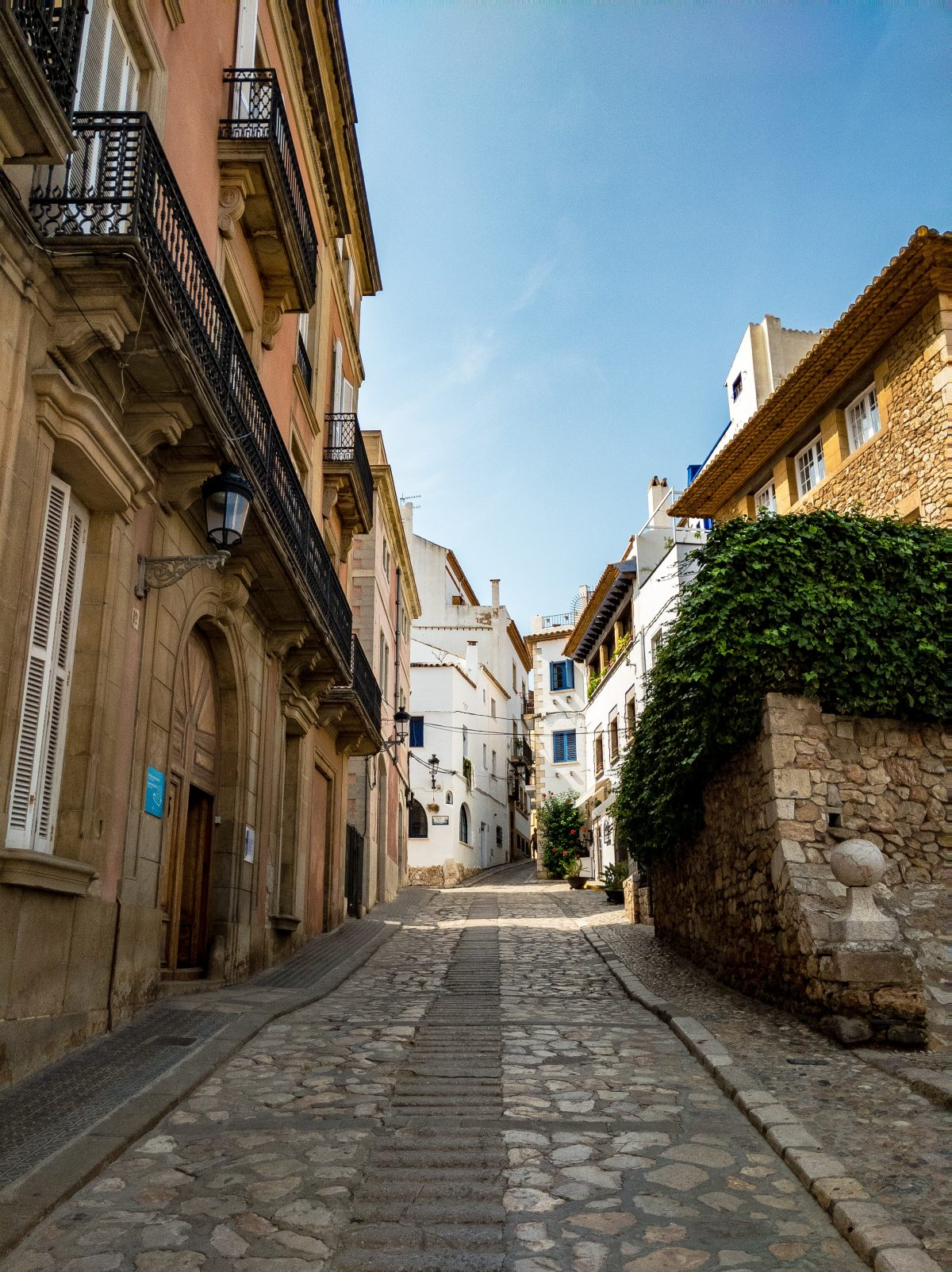 White and brown buildings line either side of a stone street in Sitges, Spain