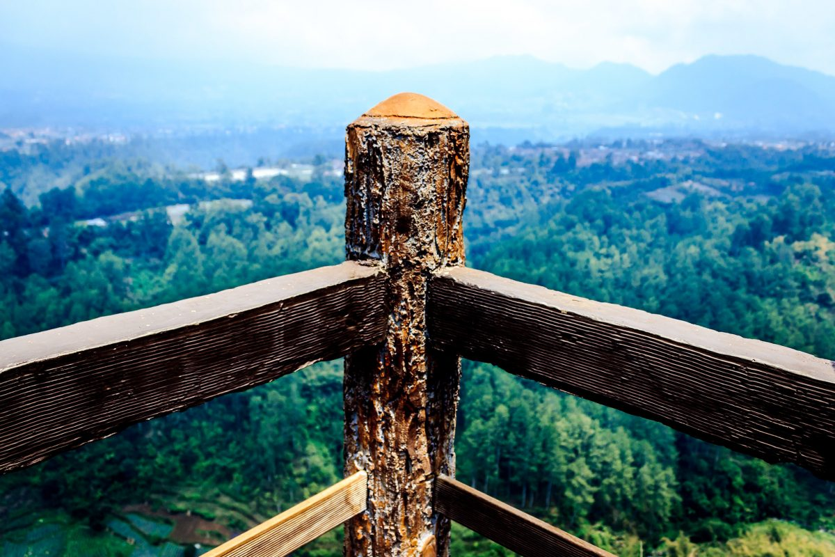 The corner of a fence overlooks the view from atop Tebing Keraton in Bandung, Indonesia