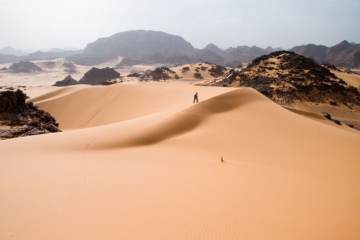 A man leaves footprints on the soft sand dunes in Tadrart Acacus