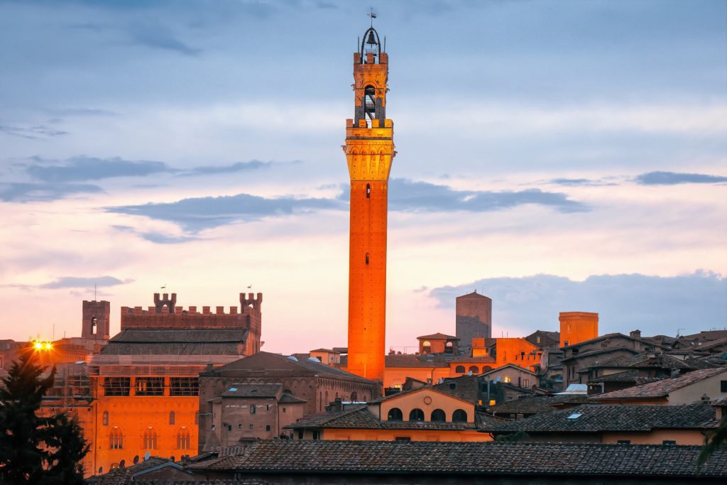 Torre-del-Mangia-siena-italy Image by pitatatu via Adobe Stock Lighted Torre del Mangia in the evening, bell tower of Palazzo Pubblico