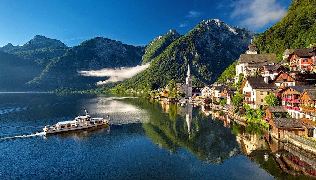 A boat cruises along the stunning Hallstatt Lake in Austria