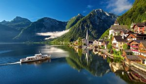 A boat cruises along the stunning Hallstatt Lake in Austria