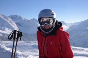 A skier wearing a ski goggle over helmer poses for the camera