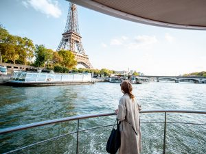Young woman enjoying beautiful landscape view on the Seine overlooking Eiffel Tower