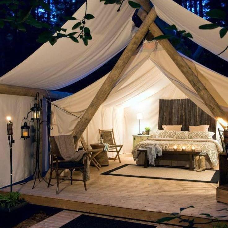 Safari-inspired tent with mattress, lounge chairs, and other amenities