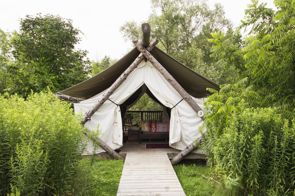 Glamping tent with tree beams and white canvas sheets as cover