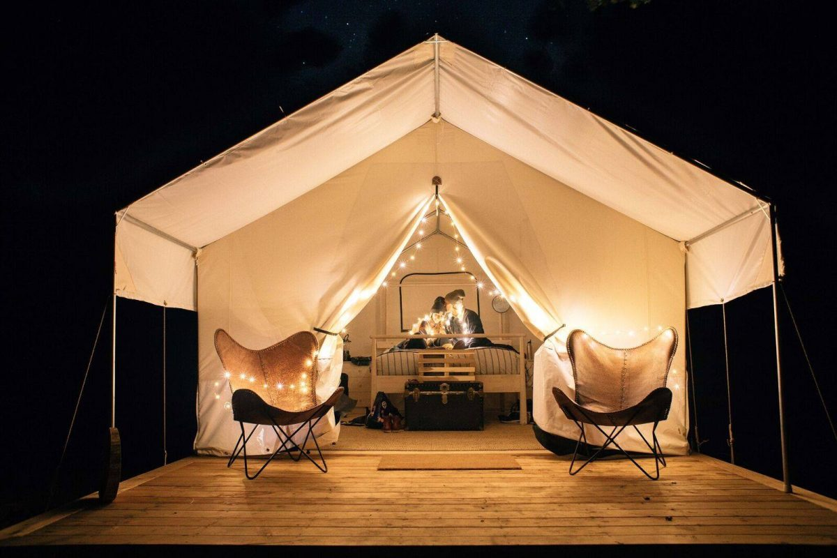 Glamping tent lit up with golden light bulbs